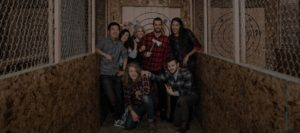 Group taking a photo at Blade and Timber Axe Throwing in Kansas City dark overlay